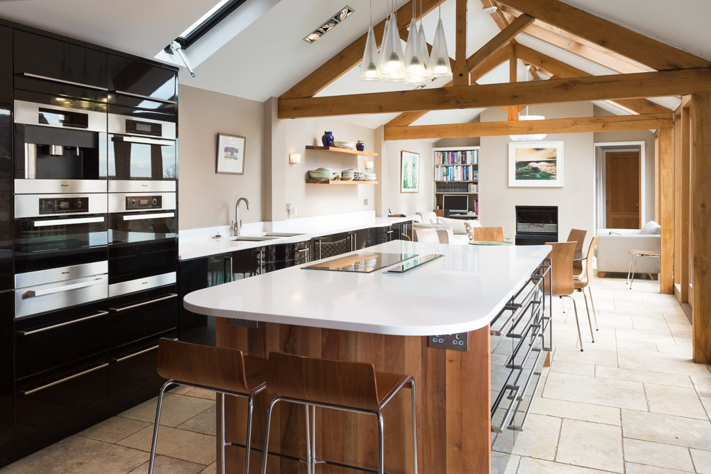 Barn oak frame kitchen extension, glossy black, travertine floor, white quartz worktops