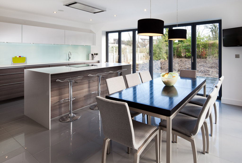 contempory kitchen in new build with bifold doors, porcelain tiled floor, glass splashback and white quartz worktop
