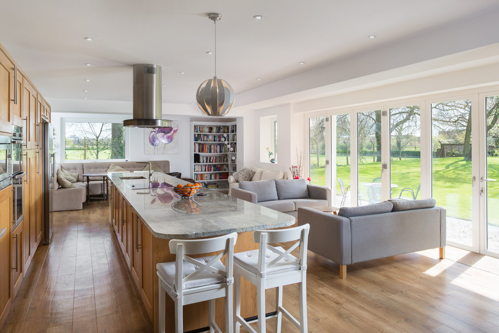 oak kitchen with white quartz worktop and large glass doors