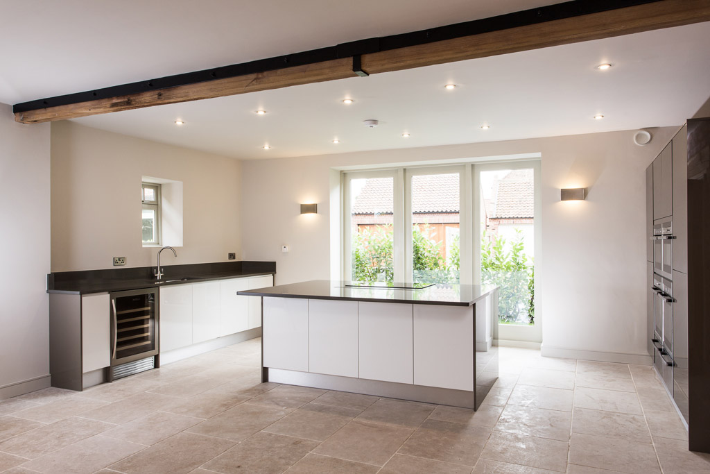 contemporary glossy white kitchen in barn conversion with grey quartz worktops